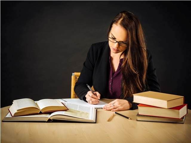 attractive-teacher-sitting-at-her-desk-writing