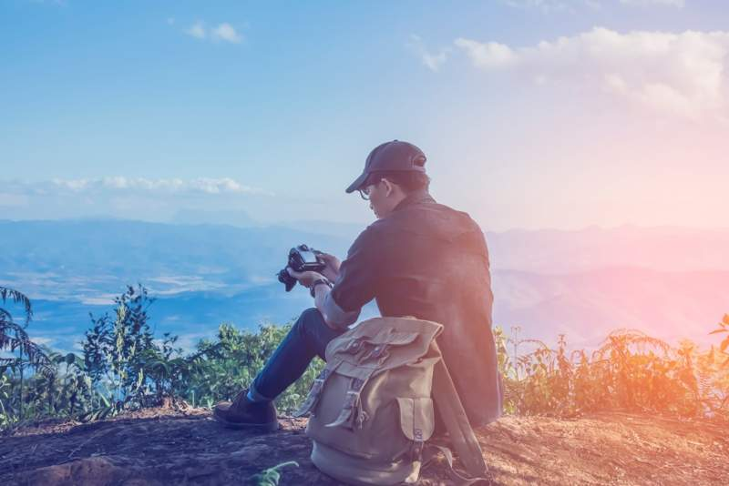 young-professional-traveler-man-with-camera-shooting-outdoor-fantastic-mountain-landscape