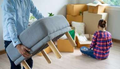 husband is carrying the furniture and his wife packing the box
