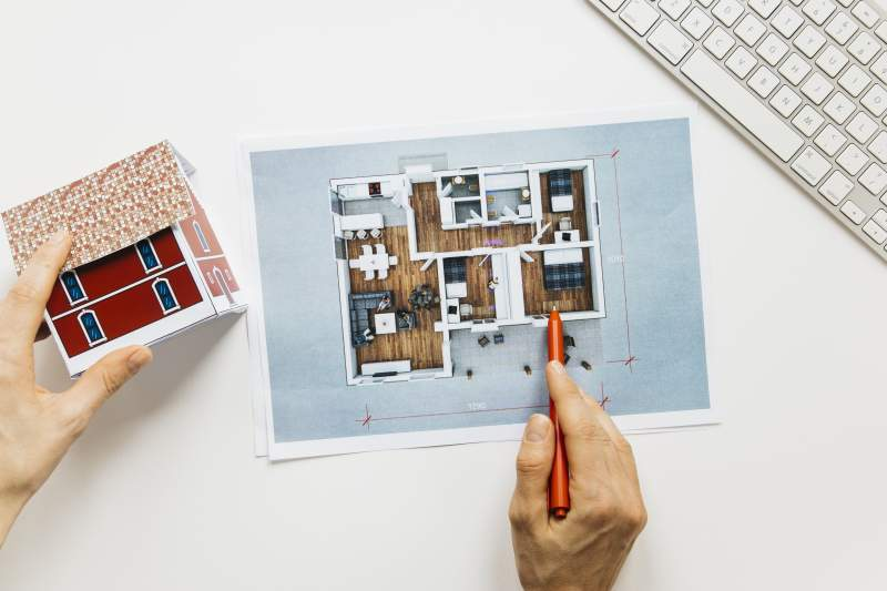 Architecture hand holding house model while checking blue print